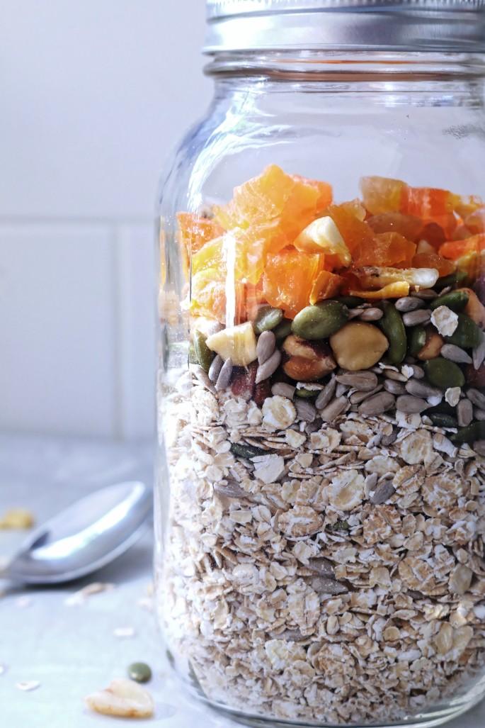 Mason jar muesli with dried fruit, oats and seeds side view