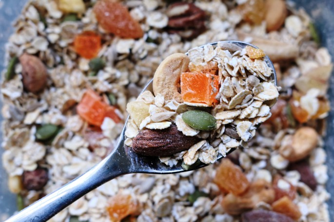 Spoonful of muesli with dried fruit, oats and seeds