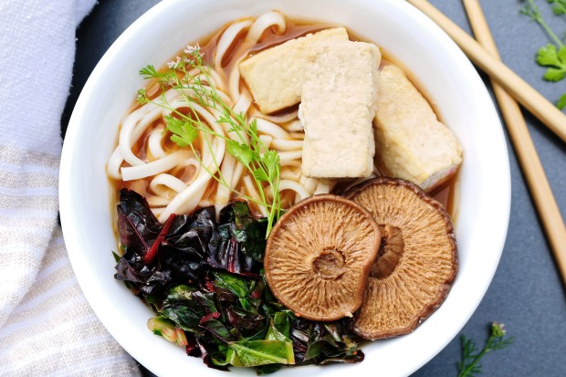 Vegan vegetarian ramen with broth soup noodles mushrooms tofu and cooked greens top view